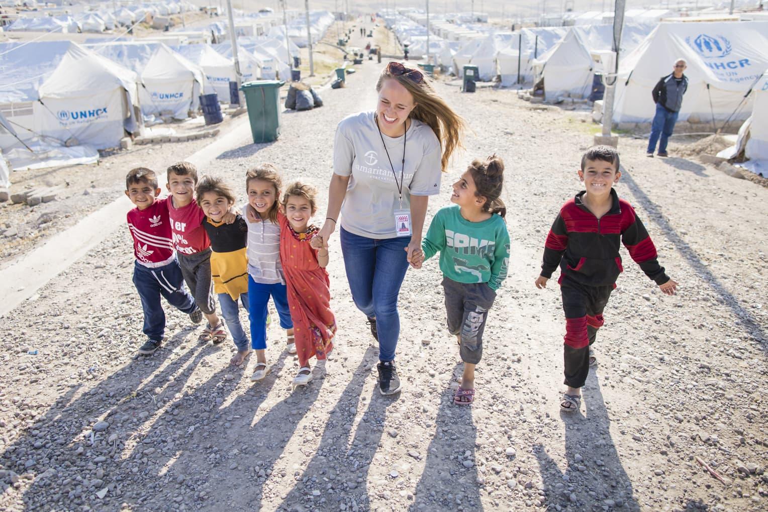Samaritan's Purse staff member walking with refugee children.